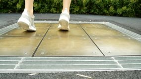 Le gambe femminili in scarpe da tennis saltano su un'attrazione musicale, premente un tasto sul pavimento produce il suono 4K stock footage