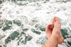 Le gambe irriconoscibili di nessun uomo della persona, sedentesi sull'orlo del pontone, all'aperto contro il mare, struttura Fotografia Stock