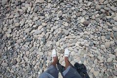 Le gambe negli shorts blu e il mackasin bianco stanno sulle piccole pietre grige Fotografia Stock