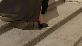 Le gambe sexy in tacchi alti neri scende le scale video d archivio