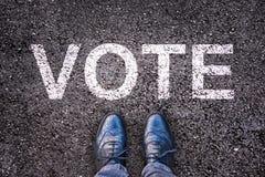 Le gambe su asfalto con il ` di parola votano il ` Fotografia Stock