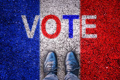 Le gambe su asfalto con la bandiera del francese e il ` di parola votano il ` Fotografia Stock