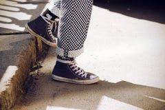 Le gambe vestite in pantaloni di plaid ed in scarpe da tennis blu discendono dal punto immagini stock libere da diritti