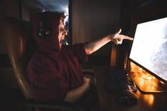 Le gamer émotif dans son capot s'assied la nuit à l'ordinateur et aux jeux vidéo de jeux, montrant un doigt sur l'écran images libres de droits
