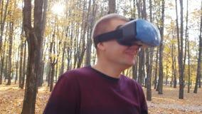 Le Gamer dans le casque de réalité virtuelle rit et a l'amusement en raison du jeu avec l'affichage tête-monté, le hmd 360 clips vidéos