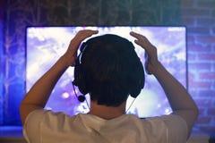 Le Gamer ou la flamme dans des écouteurs avec le microphone s'assied à la maison dans la chambre noire et joue avec des amis sur  photographie stock libre de droits