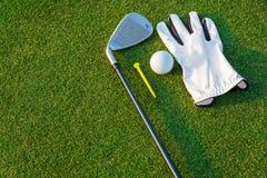 Le gant blanc d'équipement de sport de golf, la boule de golf, le club de golf et le golf jaune de pièce en t avec l'herbe verte photo libre de droits