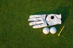 Le gant blanc d'?quipement de sport de golf, la boule de golf, le club de golf et le golf jaune de pi?ce en t avec l'herbe verte images libres de droits