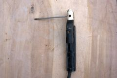Le gant protecteur de main d'usage de soudeuse tient l'électrode et le métal de soudure et étincelle La soudure est une fabricati Image stock