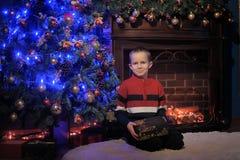 Le garçon à côté d'un arbre et d'une cheminée de Noël bleus rougeoyants Photographie stock libre de droits