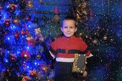 Le garçon à côté d'un arbre et d'une cheminée de Noël bleus rougeoyants Images stock