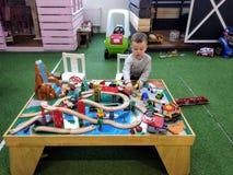 Le garçon à l'âge de 3 ans de jeux avec le chemin de fer des enfants en bois dans un coin d'enfants au centre de divertissement,  images libres de droits