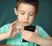 Le garçon à l'aide du comprimé, tirent à l'intérieur Photos libres de droits