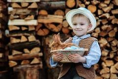 Le garçon à la ferme avec un lapin Images libres de droits