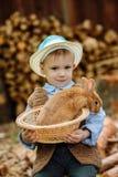 Le garçon à la ferme avec un lapin Photographie stock