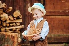 Le garçon à la ferme avec un lapin Image stock