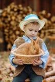 Le garçon à la ferme avec un lapin Photo libre de droits