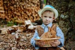 Le garçon à la ferme avec un lapin Photos libres de droits