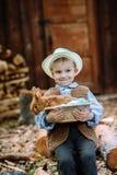 Le garçon à la ferme avec un lapin Photos stock
