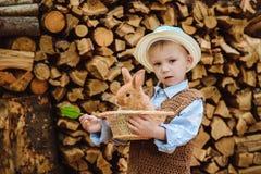 Le garçon à la ferme avec un lapin Photographie stock libre de droits