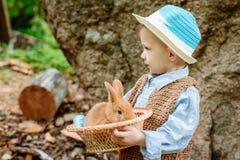 Le garçon à la ferme avec un lapin Images stock