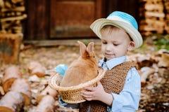 Le garçon à la ferme avec un lapin Image libre de droits