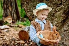 Le garçon à la ferme avec un lapin Photo stock