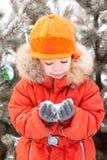 Le garçon à la promenade de l'hiver, garde la neige Photos stock