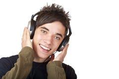 Le garçon écoutant la musique par l'intermédiaire de l'écouteur et chante Images libres de droits