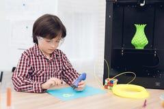 Le garçon écrit par le stylo 3d pendant une leçon dans la classe Photographie stock libre de droits