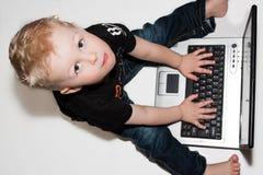 Le garçon a écrit sur l'ordinateur portatif Image libre de droits
