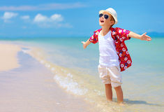 Le garçon élégant heureux apprécie la vie sur la plage d'été