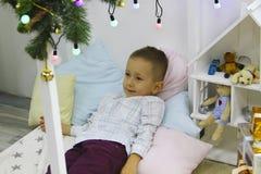 Le garçon élégant heureux se trouve sur le lit près de l'arbre de Noël photos stock