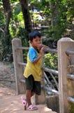 Le garçon a été distrait par le photographe se tenant sur le pont Images stock