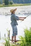 Le garçon étonné de pêcheur à la ligne jette l'amorce de la canne à pêche faite main Photo stock