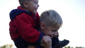 Le garçon étreignant son jeune frère et le tient sur ses épaules Rire et joie du ` s d'enfants Coucher du soleil banque de vidéos