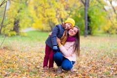 Le garçon étreint sa mère en parc d'automne Photographie stock