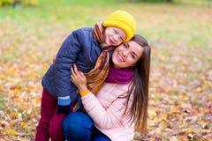 Le garçon étreint sa mère en parc d'automne Photos libres de droits