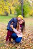 Le garçon étreint sa mère en parc d'automne Images libres de droits