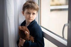Le garçon étreint son ours de nounours Se tenir prêt la fenêtre Image libre de droits