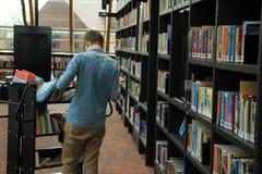 Le garçon, étudiant, travaille dans la bibliothèque municipale photos libres de droits