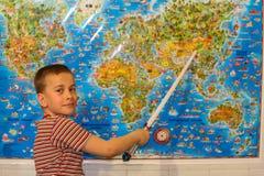 Le garçon étudie la carte photographie stock libre de droits