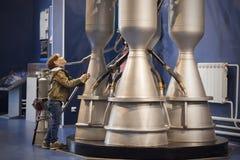 Le garçon étudie le moteur-fusées dans le musée Photographie stock