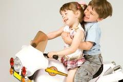Le garçon adorable et petite la fille s'asseyant sur le jouet font du vélo Image stock