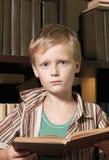 Le garçon affiche le livre avec un genre sérieux. Images libres de droits