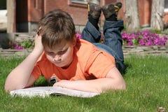 Le garçon affiche un livre images libres de droits
