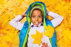 Le garçon africain s'étend dans la pile des feuilles d'automne Photo stock