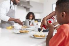 Le garçon ajoutant la crème aux crêpes comme famille apprécient le petit déjeuner dans la cuisine à la maison ensemble image libre de droits