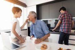 Le garçon alimente au vieil homme un gâteau Le père du ` s de garçon est derrière eux et fait la vaisselle Photographie stock