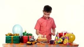 Le garçon allume des bougies sur son gâteau d'anniversaire table banque de vidéos